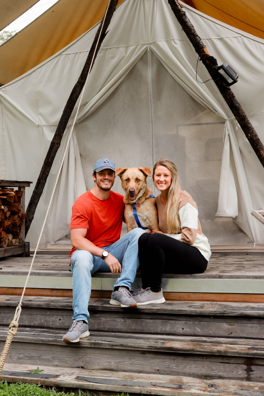 Dog friendly glamping in the heart of the Smokey Mountains Tennessee. Sitting in front of our cozy safari style tent at Under Canvas campsite.