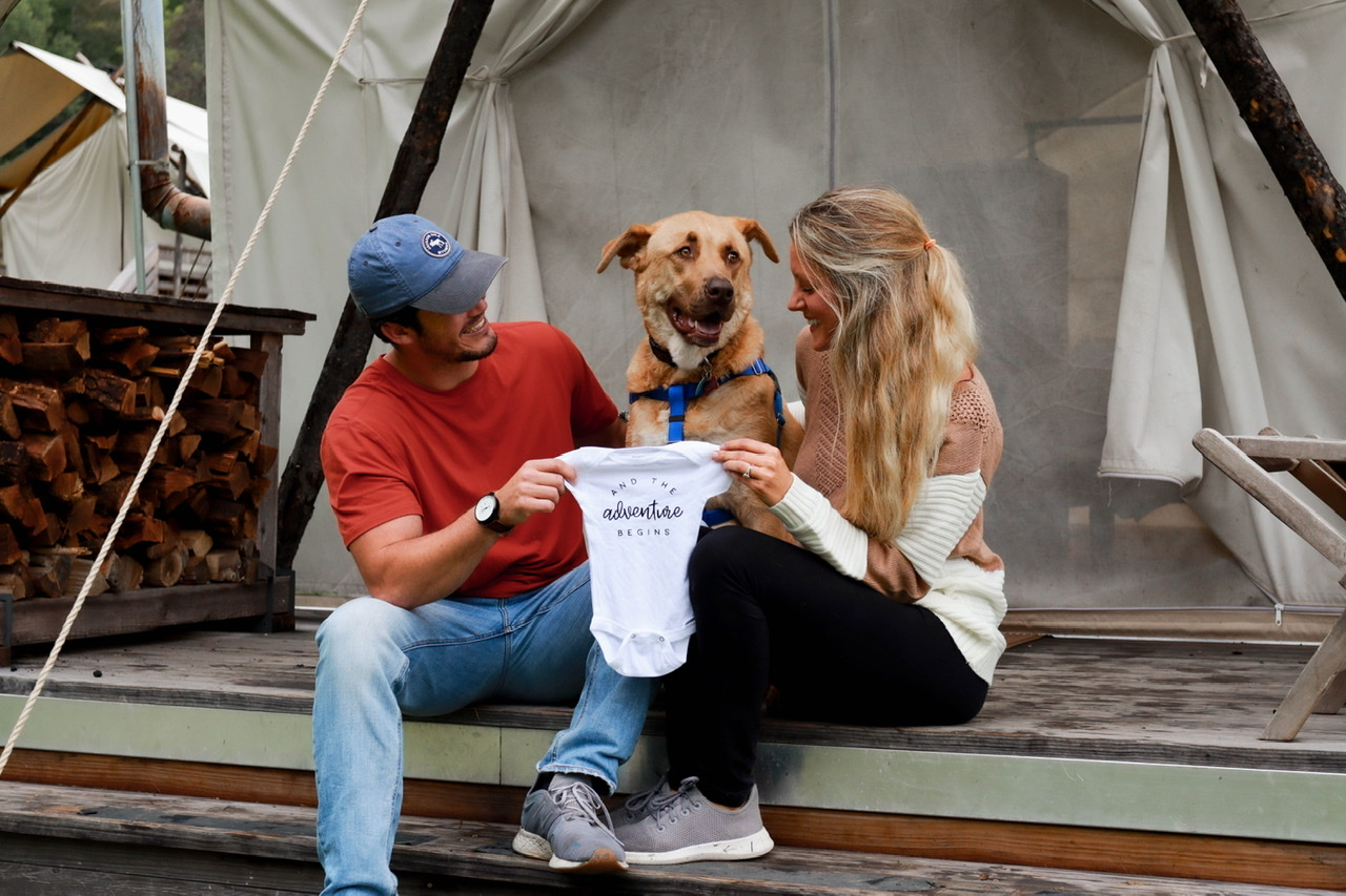 About Me Pregnancy Announcement photo taken at our glamping tent in the Smoky Mountains of Tennessee