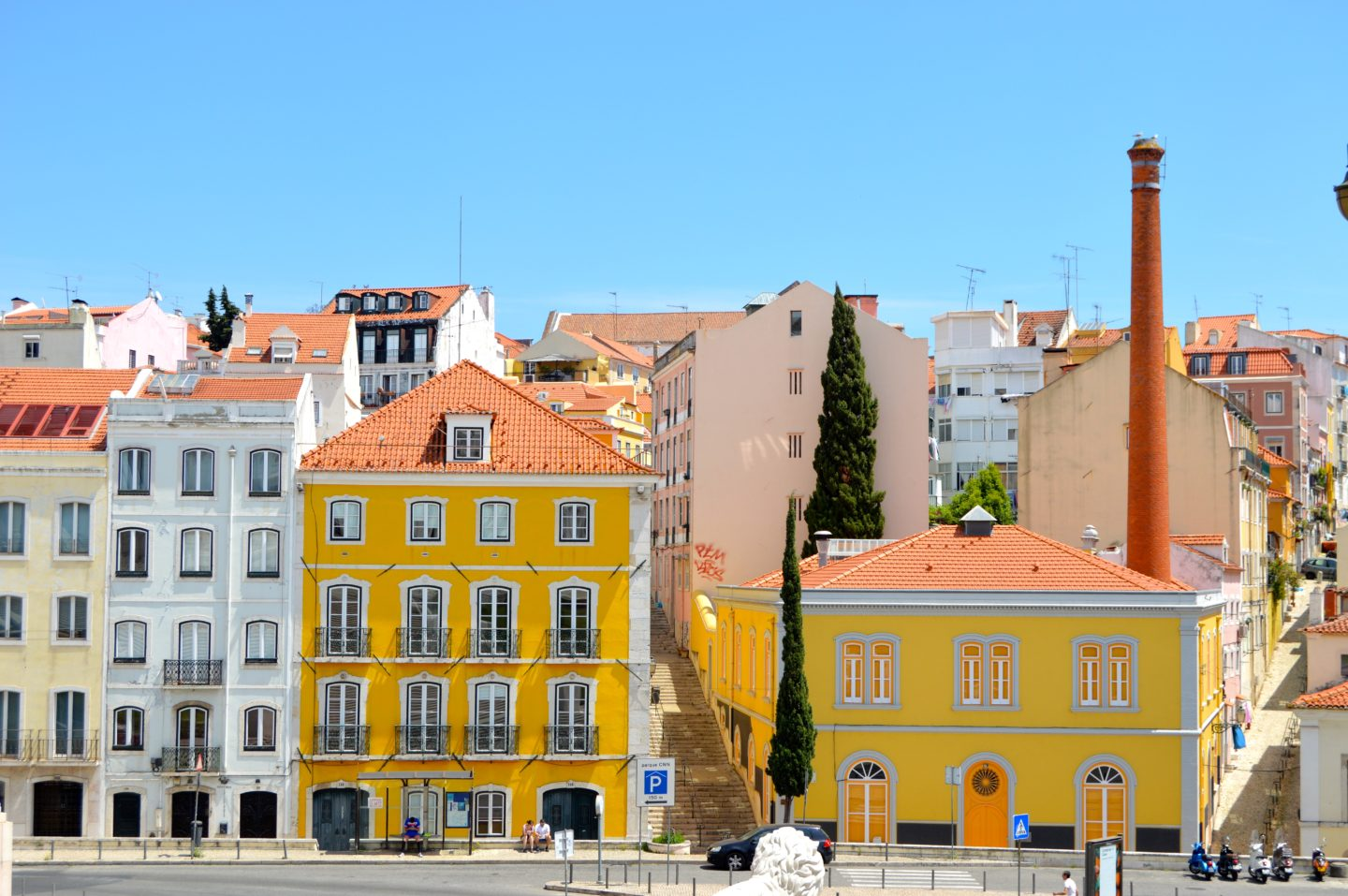 Colorful streets of Lisbon full of bright sunshine yellow paint and gorgeous pops of orange rooftops