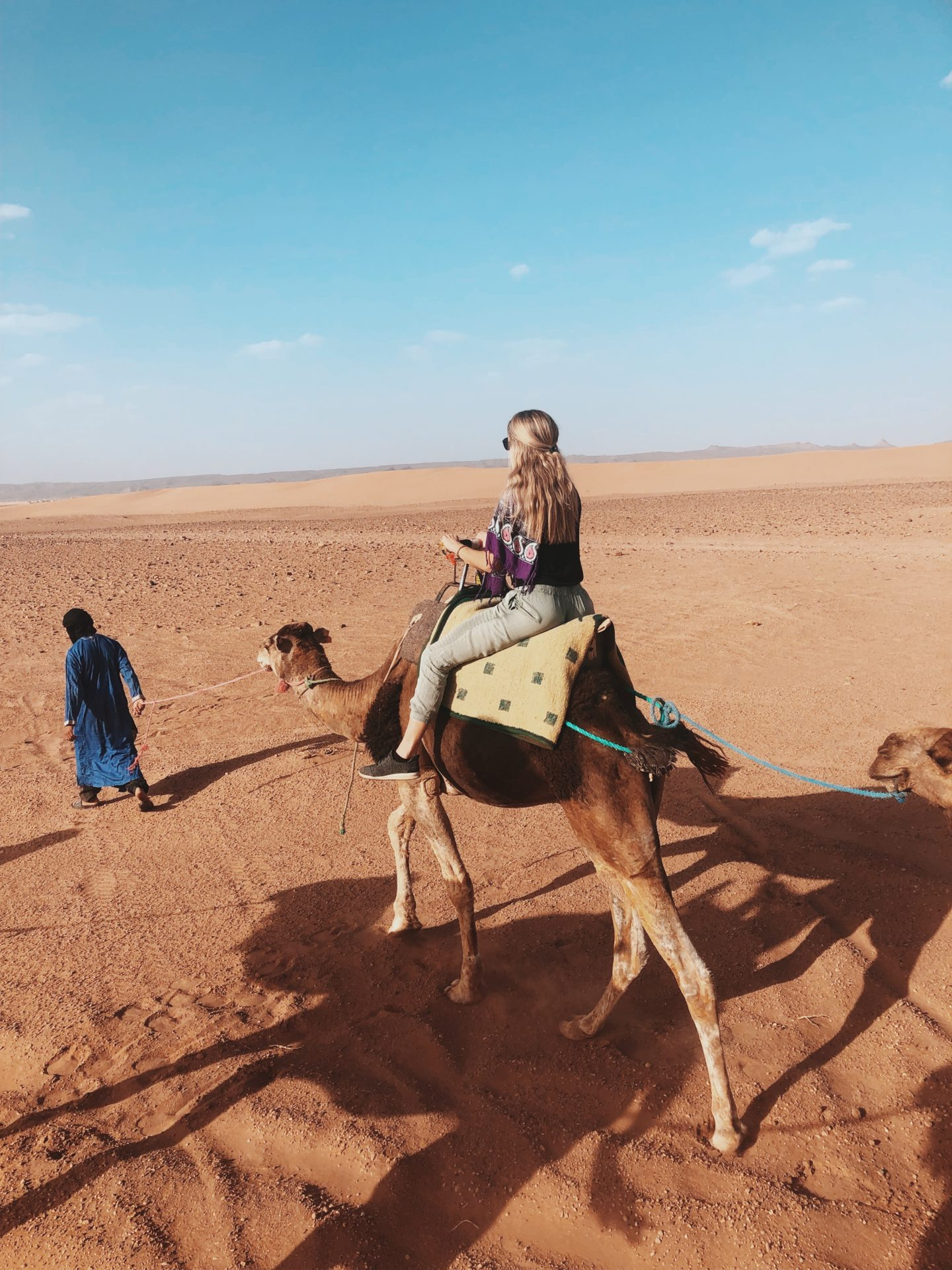 Riding a camel into the horizon of the Saharan Dessert in Morocco for a night of glamping beneath the stars.