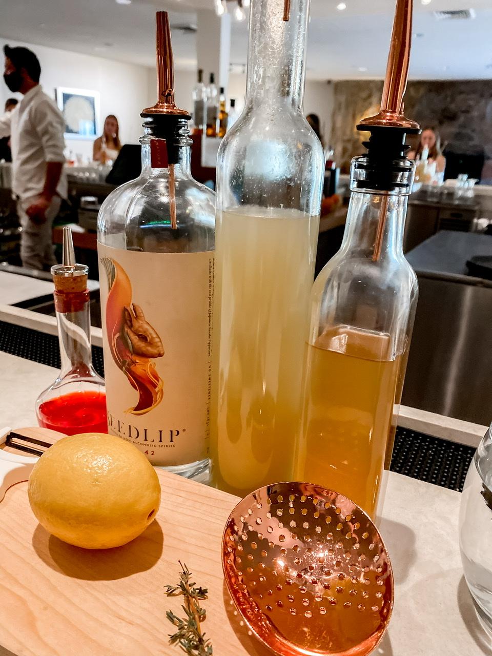 Making a healthy mocktail full of Seedlip gin , lemon and honey
